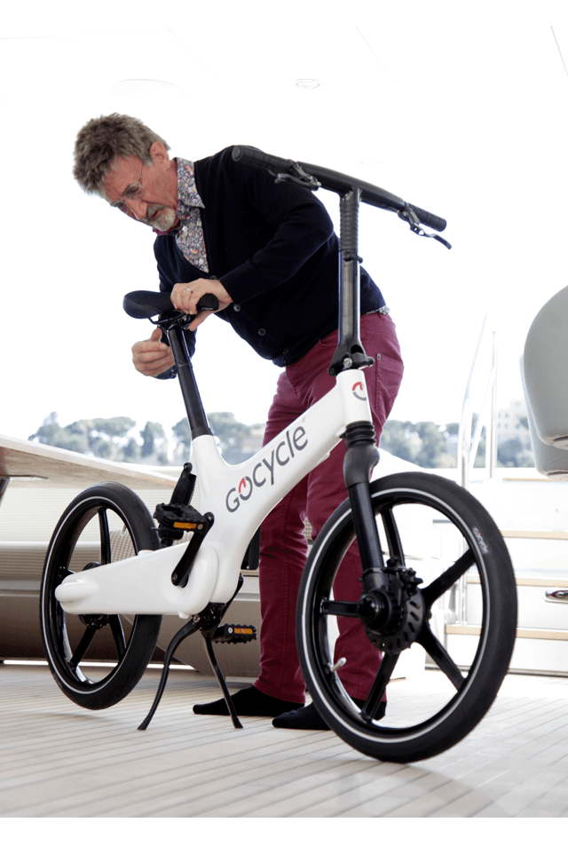 Eddie Jordan adjusting the saddle of his Gocycle on his super yacht.