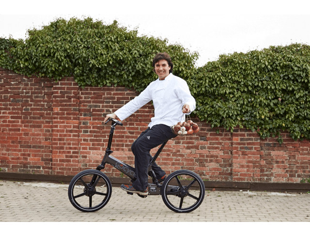 Jean-Christophe Novelli riding his Gocycle carrying a basket of onions.